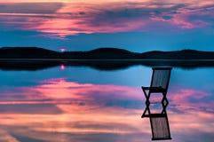 Vista escénica de la puesta del sol con la silla en agua tranquila Foto de archivo