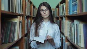 Vista esperta e moça bonita na camisa e nos vidros brancos na biblioteca escolar da colagem que seleciona o livro ler video estoque