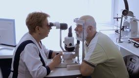 Vista examing del oculista del hombre mayor con el biomicroscope metrajes