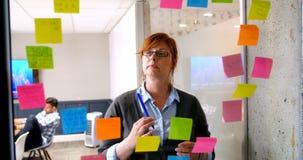 Vista executiva fêmea na nota pegajosa na parede de vidro 4k vídeos de arquivo