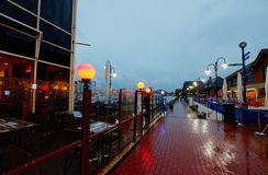 Vista exterior de barras y de restaurantes en el puerto soberano en última hora de la tarde con las luces y la lluvia fotografía de archivo libre de regalías