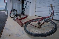 A vista exterior de bicicletas do rolo de amish ou os 'trotinette's inclinam-se contra uma casa fotos de stock