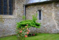 Vista exterior de una iglesia vieja, medieval vista con algunos arbustos color de rosa cerca de la entrada del pórtico fotografía de archivo libre de regalías