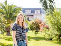 Vista fêmea consideravelmente atrativa dos jovens ao redor, andando na rua da cidade tropical com palmeiras e os carros estaciona fotos de stock royalty free