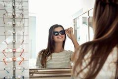 Vista fêmea europeia moreno feliz atrativa no espelho ao tentar em óculos de sol na loja do ótico, sorrindo foto de stock royalty free