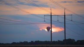 Vista fantástica del globo enorme del aire caliente que vuela sobre campo en la puesta del sol, sueños metrajes