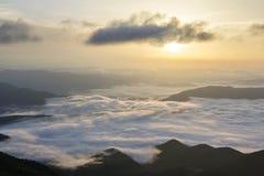 A vista fantástica do vale da montanha coberta com o baixo inchado branco como a neve nubla-se o esticão ao horizonte nevoento so foto de stock