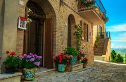 Vista fiorita della via e dell'entrata in Toscana, Pienza, Italia Fotografia Stock