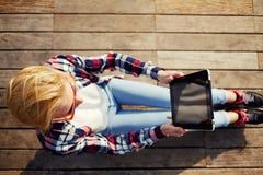 Vista fotografante turistica femminile sveglia che si siede sul pavimento di legno all'aperto Fotografie Stock Libere da Diritti