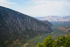Vista fresca del paesaggio della valle del pendio di montagna di Parnassus, oliveti verdi attraverso il mare ionico con il fondo  fotografia stock libera da diritti