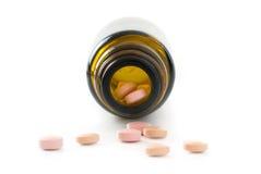 Vista frontal em uma garrafa da farmácia e no último isolador cor-de-rosa dos comprimidos imagens de stock royalty free