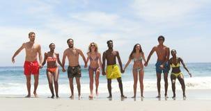 Vista frontale degli amici razza mista che saltano insieme sulla spiaggia 4k archivi video