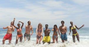 Vista frontale degli amici razza mista che saltano insieme sulla spiaggia 4k video d archivio