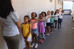 Vista frontale degli scolari con l'insegnante che sta nella fila con le loro mani sulla spalla in corridoio immagini stock libere da diritti