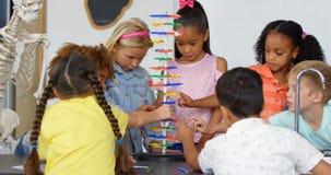 Vista frontale degli scolari razza mista che studiano circa il modello della molecola del DNA nell'aula 4k stock footage