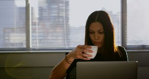 Vista frontale del caffè bevente della giovane donna di affari caucasica mentre lavorando al computer portatile in ufficio 4k archivi video