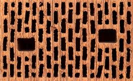 Vista frontale del mattone rosso con i buchi neri Immagini Stock