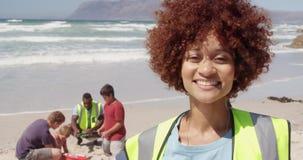 Vista frontale del volontario femminile afroamericano che esamina macchina fotografica sulla spiaggia 4k stock footage