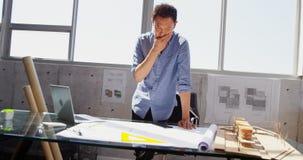 Vista frontale dell'architetto maschio asiatico con la mano su funzionamento del mento allo scrittorio in ufficio 4k video d archivio