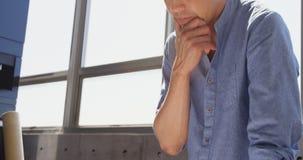 Vista frontale dell'architetto maschio asiatico con la mano su funzionamento del mento allo scrittorio in ufficio 4k stock footage