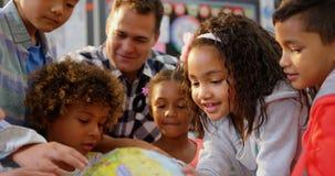 Vista frontale dell'insegnante maschio caucasico che insegna ai bambini circa il globo nell'aula 4k video d archivio