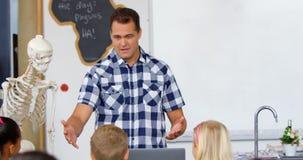 Vista frontale dell'insegnante maschio caucasico che spiega circa il modello di scheletro umano nell'aula 4k archivi video