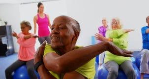 Vista frontale dell'istruttore femminile caucasico che forma la gente senior nell'esercizio allo studio 4k di forma fisica archivi video