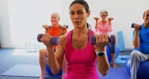Vista frontale dell'istruttore femminile che forma la gente senior nell'esercizio allo studio 4k di forma fisica video d archivio