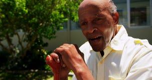 Vista frontale dell'uomo senior asiatico attivo che si siede con il bastone da passeggio nel giardino della casa di cura 4k archivi video