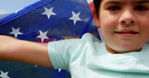Vista frontale della bandiera americana caucasica della tenuta dello scolaro nel campo da giuoco 4k della scuola stock footage