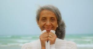 Vista frontale della condizione afroamericana senior attiva felice della donna sulla spiaggia 4k video d archivio