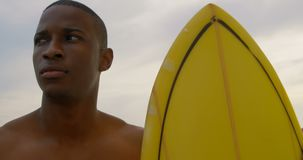 Vista frontale della condizione maschio afroamericana del surfista con il surf sulla spiaggia 4k archivi video