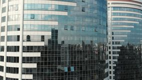 Vista frontale della costruzione di vetro Riflessione su un edificio per uffici moderno Pareti di vetro e finestre nel distretto  stock footage