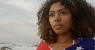 Vista frontale della donna afroamericana avvolta nella condizione della bandiera americana sulla spiaggia 4k video d archivio