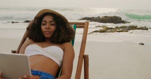 Vista frontale della donna afroamericana che per mezzo della compressa digitale sulla spiaggia 4k stock footage