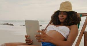 Vista frontale della donna afroamericana che per mezzo della compressa digitale sulla spiaggia 4k video d archivio