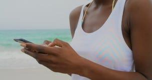 Vista frontale della donna afroamericana che per mezzo del telefono cellulare sulla spiaggia 4k stock footage