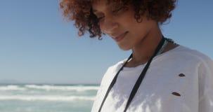 Vista frontale della donna afroamericana che per mezzo del telefono cellulare sulla spiaggia 4k video d archivio