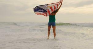 Vista frontale della donna afroamericana con la bandiera americana d'ondeggiamento che balla sulla spiaggia 4k video d archivio