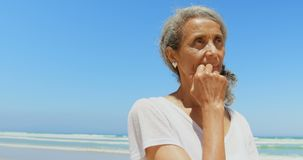 Vista frontale della donna afroamericana senior attiva premurosa con la mano sulla condizione del mento alla spiaggia 4k video d archivio