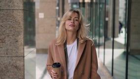 Vista frontale della donna bionda che cammina con il caffè in via di autunno archivi video