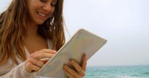 Vista frontale della donna caucasica che per mezzo della compressa digitale sulla spiaggia 4k video d archivio