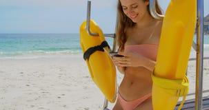 Vista frontale della donna caucasica che per mezzo del telefono cellulare sulla spiaggia 4k stock footage