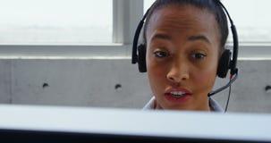 Vista frontale della donna di affari afroamericana che parla sulla cuffia avricolare allo scrittorio in un ufficio moderno 4k archivi video