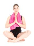 Vista frontale della donna di seduta con l'asciugamano, le mani insieme e la mediazione porpora Fotografie Stock Libere da Diritti