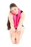 Vista frontale della donna di seduta con l'asciugamano porpora, allungante con le sue mani ai suoi piedi Immagini Stock