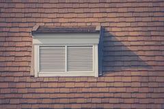 Vista frontale della finestra di legno bianca sul tetto della casa di legno nello stile d'annata alla campagna Immagini Stock Libere da Diritti