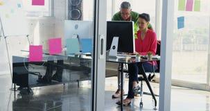 Vista frontale della gente di affari caucasica che discute sopra il computer allo scrittorio nell'ufficio 4k video d archivio
