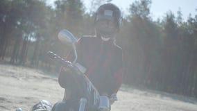 Vista frontale della ragazza nella condizione del casco al motociclo davanti all'abetaia al sole Hobby, viaggiante archivi video