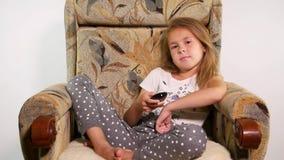 Vista frontale della ragazza teenager che si siede nella sedia che guarda la TV annoiata video d archivio